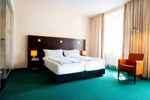 A bed or beds in a room at Flemings Hotel München-City