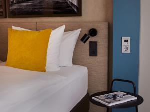 Een bed of bedden in een kamer bij Hotel Mondial am Dom Cologne MGallery