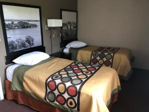 A bed or beds in a room at Super 8 by Wyndham Kingston