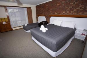 A bed or beds in a room at Donald Motor Lodge