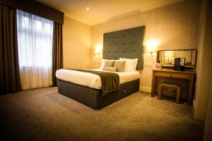 A bed or beds in a room at Heywood Spa Hotel