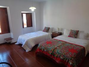 A bed or beds in a room at Hospedaria Senhora do Carmo