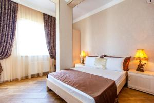 A bed or beds in a room at Akropol Apartments
