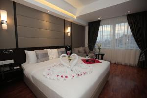 A bed or beds in a room at Harmony Phnom Penh Hotel