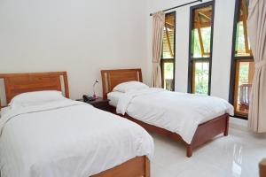 A bed or beds in a room at Spring Hill Boutique Hotel Ruteng