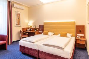 A bed or beds in a room at Austria Classic Hotel Wien