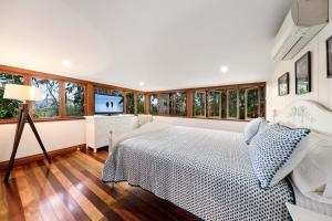 A bed or beds in a room at Poinciana Lodge