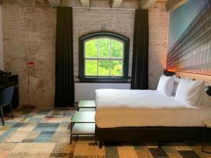 A bed or beds in a room at Onderwijshotel De Rooi Pannen Breda