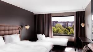 A bed or beds in a room at Radisson Blu Marina Palace Hotel, Turku