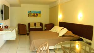 A bed or beds in a room at Natal Praia Hotel