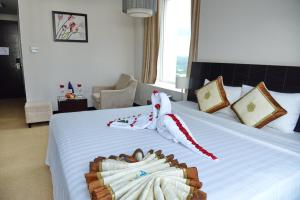 A bed or beds in a room at Sai Gon Ban Me Hotel