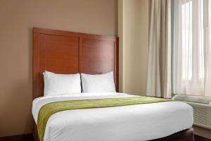 A bed or beds in a room at Comfort Inn & Suites near JFK Air Train
