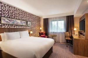 A bed or beds in a room at Leonardo London Heathrow Airport