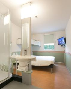 A bed or beds in a room at ibis budget Bordeaux Aéroport