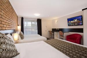 A bed or beds in a room at Gateway Motor Inn Warrnambool