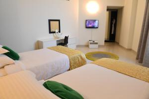A bed or beds in a room at Gulf Suites Hotel Amwaj