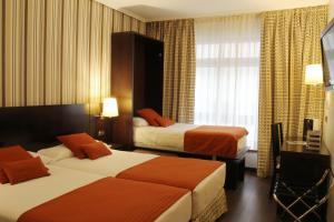 A bed or beds in a room at Hotel Conde Duque Bilbao