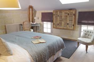 A bed or beds in a room at Logis de la Cadène