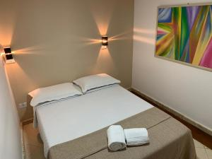 A bed or beds in a room at Praia do Forte Suites