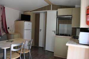 A kitchen or kitchenette at Camping du Bourg