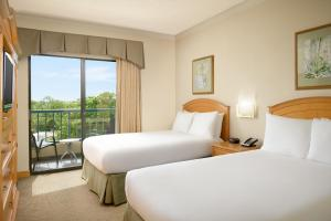 A bed or beds in a room at Hilton Boca Raton Suites