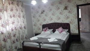 Un pat sau paturi într-o cameră la Pensiunea Duet