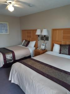 A bed or beds in a room at Harbour Light Motel