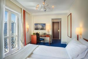 A bed or beds in a room at Augustin Hotel