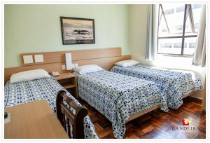 A bed or beds in a room at Bandeira Hotel