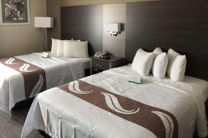 A bed or beds in a room at Quality Inn & Suites Roanoke - Fort Worth North