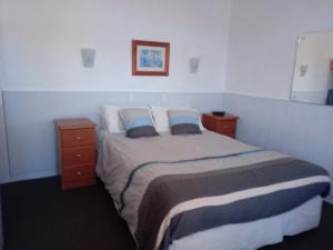 A bed or beds in a room at Travellers Rest Motel
