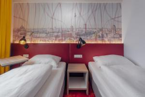 A bed or beds in a room at Campanile Berlin Brandenburg Airport