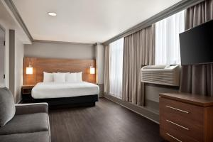 A bed or beds in a room at Days Inn by Wyndham Vancouver Downtown