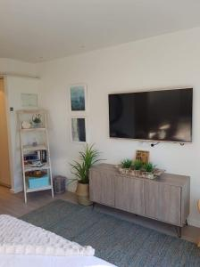 A television and/or entertainment center at Cowes Partner Retreat - Beachfront