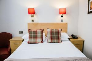A bed or beds in a room at Lindum Hotel