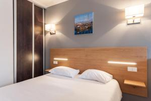 A bed or beds in a room at Residhotel Le Grand Prado