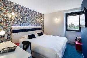 Un ou plusieurs lits dans un hébergement de l'établissement Hotel l'Ortega Rennes Aeroport