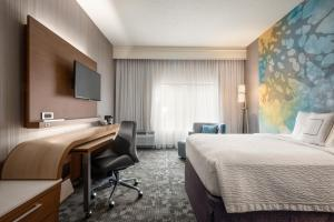 A bed or beds in a room at Courtyard by Marriott Dayton North