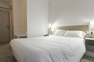 A bed or beds in a room at Hotel du Clocher