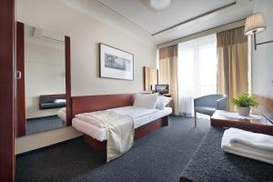 A bed or beds in a room at Hotel Kladno
