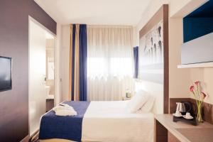 A bed or beds in a room at Mercure Roma Centro Colosseo