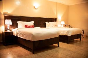 A bed or beds in a room at Urban Point Hotel
