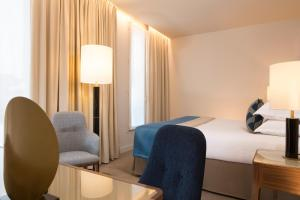 A bed or beds in a room at Le Tsuba Hotel