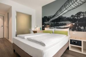 A bed or beds in a room at Super 8 by Wyndham Oberhausen am Centro