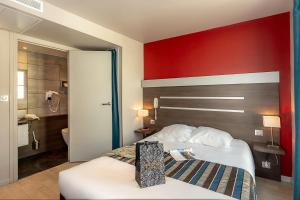 A bed or beds in a room at Hotel Terminus Saint-Charles
