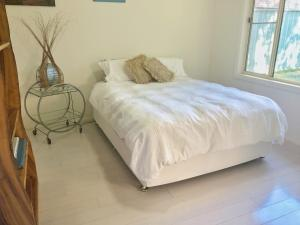 A bed or beds in a room at Nobbys Beach Retreat