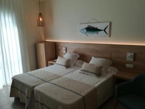 A bed or beds in a room at Hotel Tamariu
