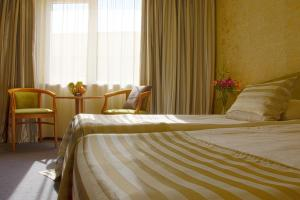 A bed or beds in a room at Triada Hotel