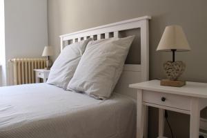 A bed or beds in a room at La Folie des Remparts