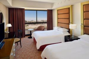 A bed or beds in a room at Petra Marriott Hotel